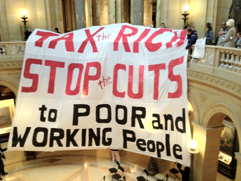 Huge white cloth banner held up inside the state capitol - (in red) Tax the Rich. Stop the Cuts (in black) to Poor and Working People