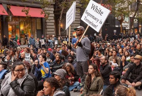 huge crowd sitting down in the street with a black man holding a picket sign saying White Supremacy is terrorism