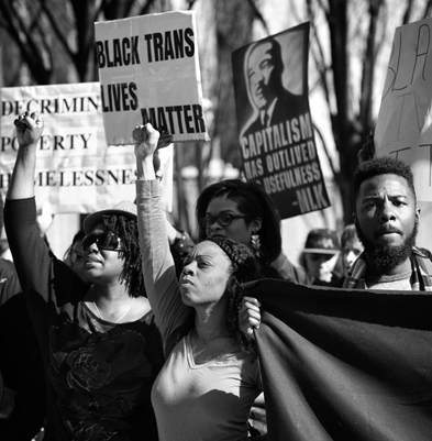 Black women and men with fists raised holding signs saying Black Trans Lives Matter