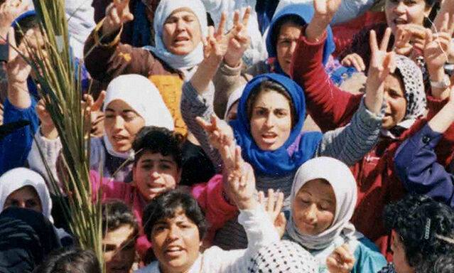 Crowd of Palestinian women with hands raised in V sign at the first Intifada in 1980, includes Naila Ayesh