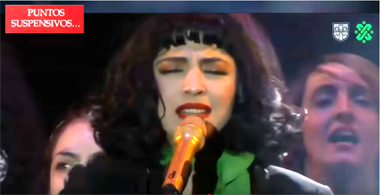 dark-haired women singing into golden microphone with other women singing behind her