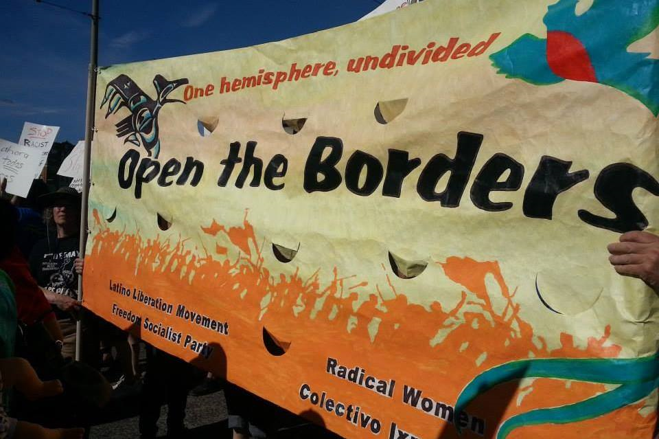 Yellow banner with orange silhouettes of protesters acros the bottom -saying One hemisphere undivided - Open the Borders